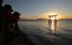 鳥居の内側から昇る朝日を撮影するカメラマン(18日午前7時15分、高島市鵜川)