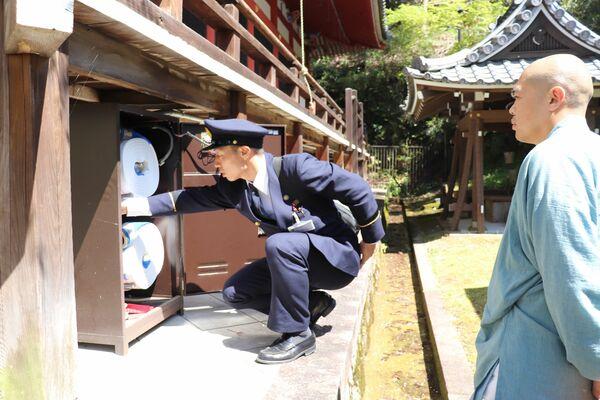 文化財の防火指導で、消火用のホースを点検する消防署員(左)。職員削減に伴い、防火活動への影響を心配する声も出ている(2019年4月、京都市左京区・永観堂)