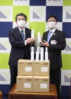 アルコール消毒液を寄贈した三菱製紙の楠田京都工場長(左)=長岡京市役所