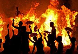 燃えさかるたいまつの前で乱舞し、気勢を上げる若衆たち(11日午後9時5分、滋賀県守山市・勝部神社)