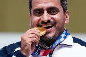射撃男子エアピストルで優勝し、金メダルにかみついてみせるイラン代表のジャバド・フォルギ=24日、自衛隊朝霞訓練場(AP=共同)