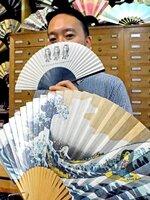 アマビエを描いた扇子を手に、飛沫感染防止を意識したエチケットを提案する大西さん(京都市中京区・大西京扇堂)