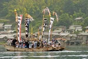 八坂神社などののぼりを立て、舟屋が立ち並ぶ湾内を進む祭礼船(伊根町・伊根湾)