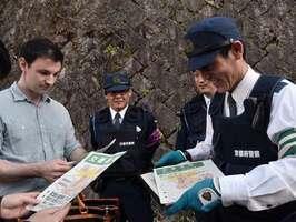 サルのかみつき被害に遭わないよう、外国人観光客に注意を呼び掛ける東山署員(京都市東山区)