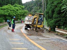 崩れ出た土砂を除去する作業員ら(8日午前10時、高島市マキノ町野口・国道161号)