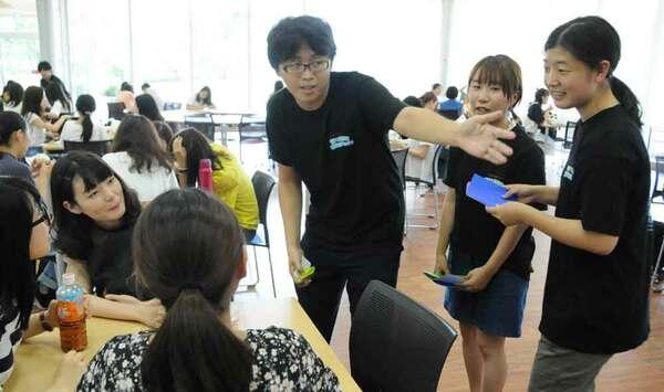 サロンにいる学生に折り紙を配り、折り鶴を作ってもらうよう頼む学生プロジェクトのメンバーたち(宇治市槙島町・京都文教大)