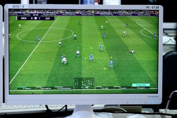 選手たちが操作するサッカーゲームの画面。インターネットを経由し、知らない相手と対戦している