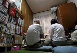 石田さんの部屋に設けられた祭壇の前で、遺影を見つめる両親。本棚には手がけた作品のDVDも並ぶ(京都市伏見区)