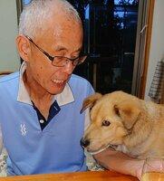 小原英明さんに寄り添う愛犬のじょん=小原さん提供