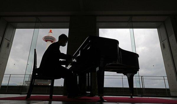 京都駅ビルのピアノを演奏する男性。京都タワーが見える絶好のロケーションも魅力の一つだ(3月6日、京都市下京区)