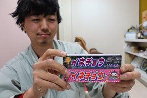 伊根町内だけで販売されているパロディー商品「イネチョウ」を持つ澤田さん(京都府伊根町日出)