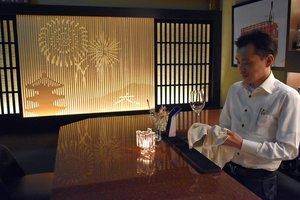祇園地区で営むバーの営業再開に向けてグラスを拭く芦田さん(19日、京都市東山区)