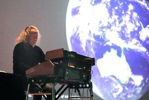 宇宙の映像に合わせ演奏する喜多郎さん(24日午後4時、京都市左京区・京都大百周年時計台記念館)