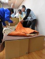 高齢の避難者を受け入れるため、段ボールでベッドを作る住民たち(京都府亀岡市馬路町・馬路生涯学習センター)