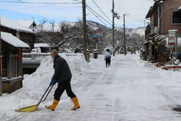 降り積もった雪を川横に集める住民(8日午前9時半、京丹後市峰山町御旅)