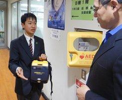 校内の自動体外式除細動器(AED)について教員と話す大川さん=京都市左京区・東山中