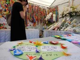 千羽鶴が飾られた献花台で祈りをささげるファンら(8月8日午前10時50分、京都市伏見区)