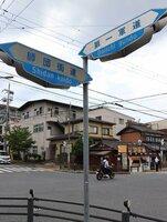 龍谷大の南東角にある道路標識。陸軍とともにあったまちの歴史を伝える道も、今は自家用車や市バスが行き交う(京都市伏見区)