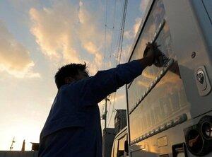 自販機を掃除するルートドライバーの岡さん。早朝から始まった業務は夕暮れになっても続く(京都府内)