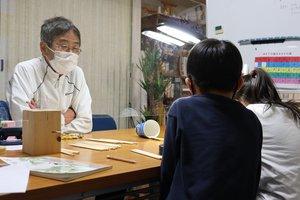 子どもに勉強を教える枡田さん(左)=京都府与謝野町