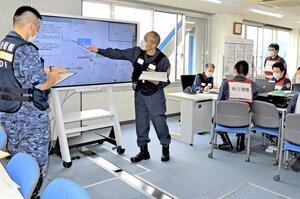 行方不明者など現場の状況を海上自衛隊の連絡員(左)に伝える8管担当者(舞鶴市下福井・舞鶴港湾合同庁舎)