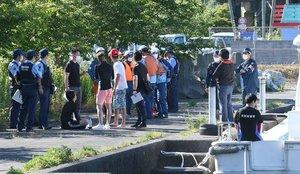 転覆したクルーザーから救助された人たちに話を聞く警察官ら(6月7日、大津市・近江舞子中浜水泳場付近)