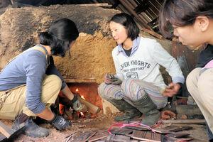 窯に火を入れた後に木をくべる「炭焼人」のメンバー(南丹市美山町下)
